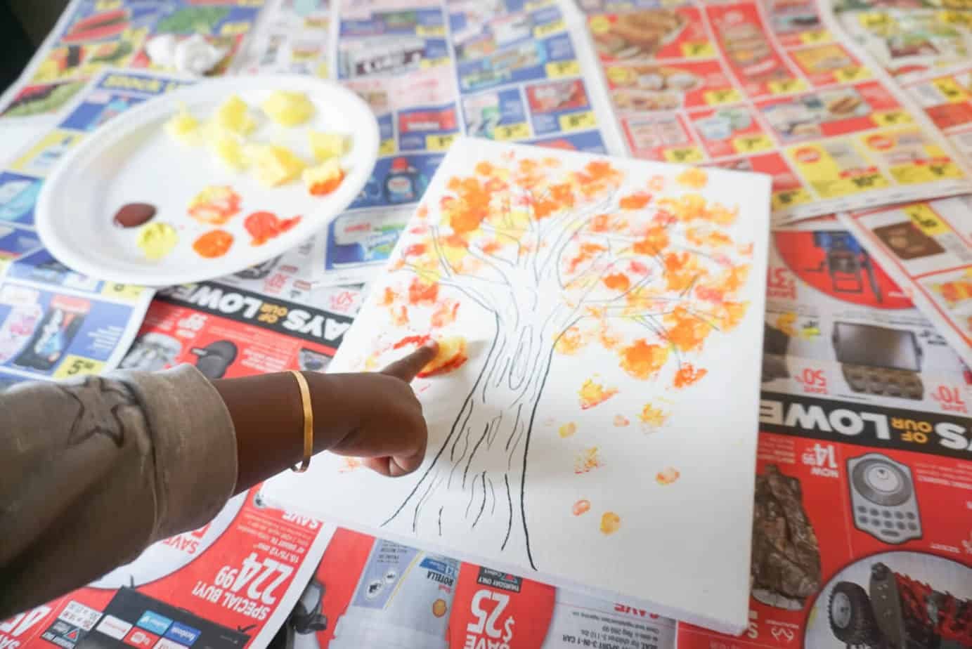 toddler finger painting a fall tree with colorful leaves
