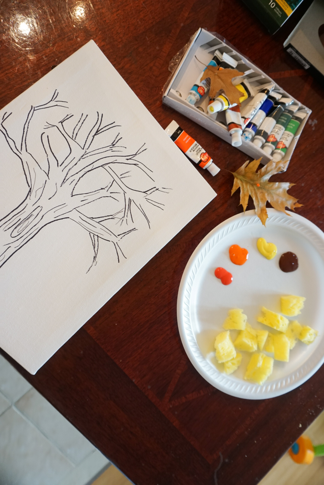 Painting supplies like paint, paint brush, paint sponges, canvas with a tree drawing.