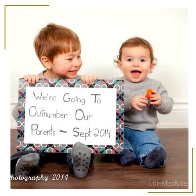 two toddler boys holding sign to announce new baby