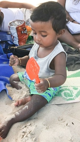 baby playing with beach toys at the beach in sand
